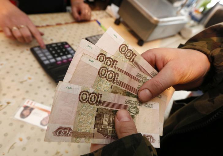 Покупатель держит в руках рублевые купюры в магазине в поселке Верхняя Бирюса близ Красноярска 23 января 2015 года. Рубль вырос при открытии биржевых торгов вторника на фоне слабого доллара и стабильной нефти, а также за счет снижения градуса напряженности на востоке Украины. REUTERS/Ilya Naymushin